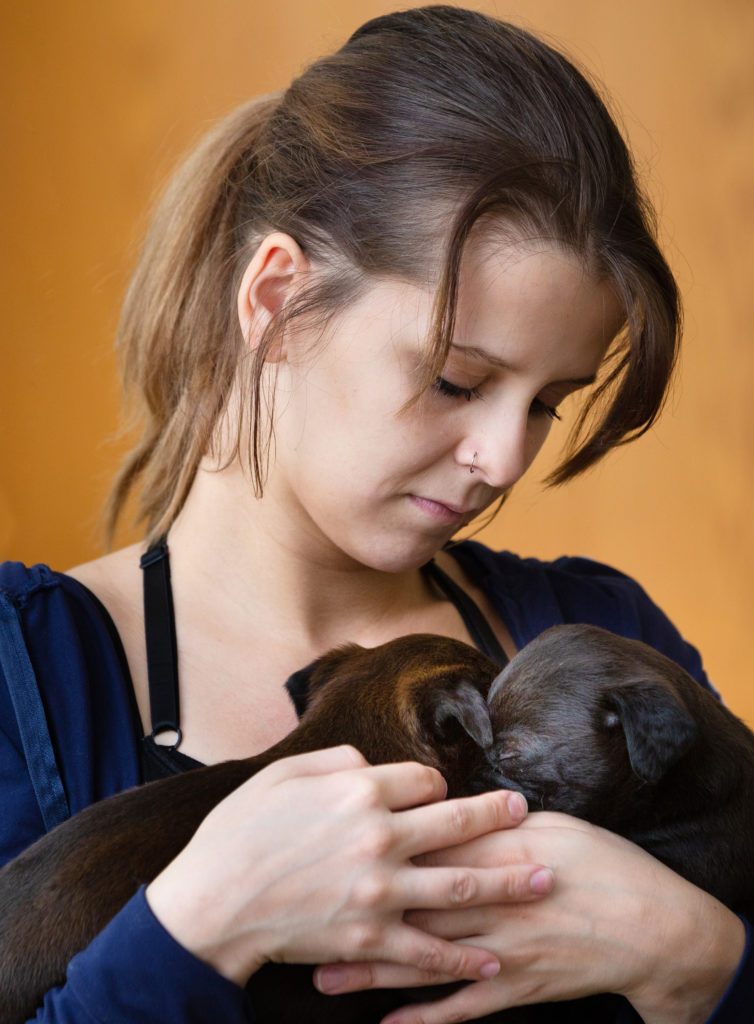 Young woman holding two brown puppies in her arms.