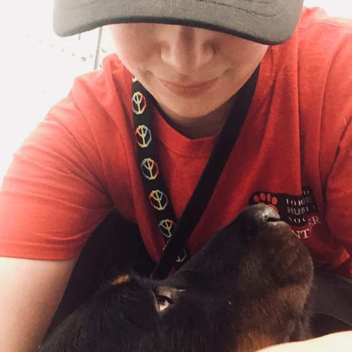 female volunteer cuddling black and brown dog